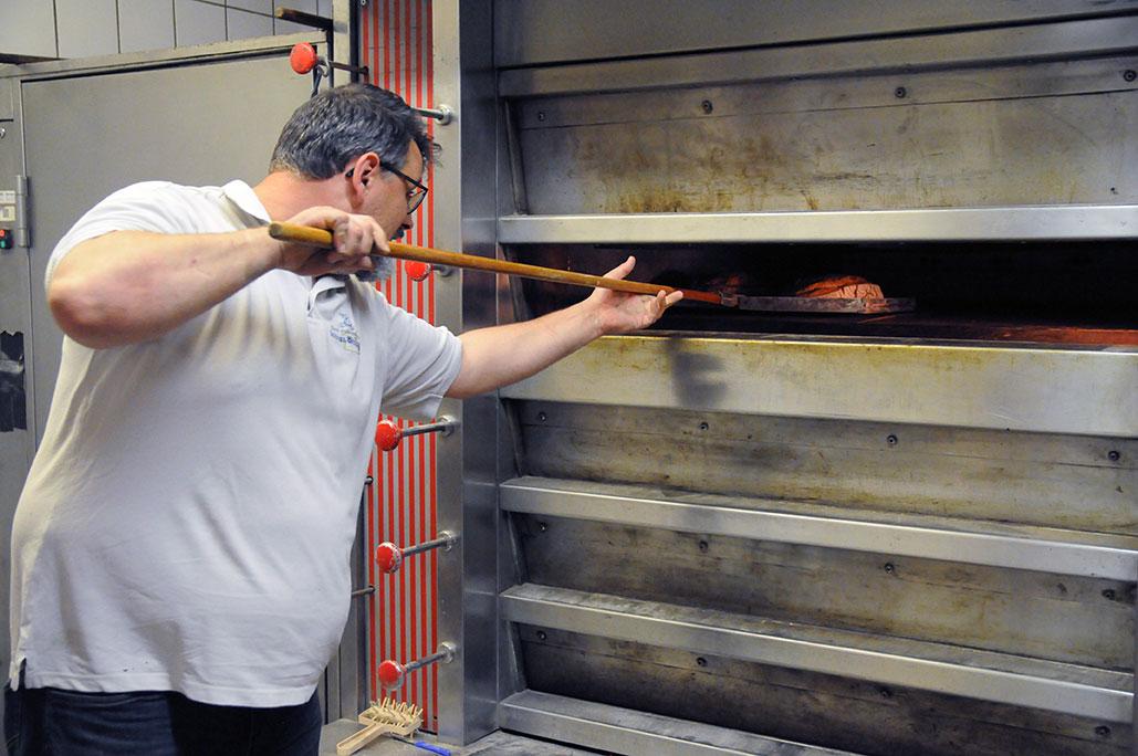 Bäckermeister schiebt Brot in Backofen